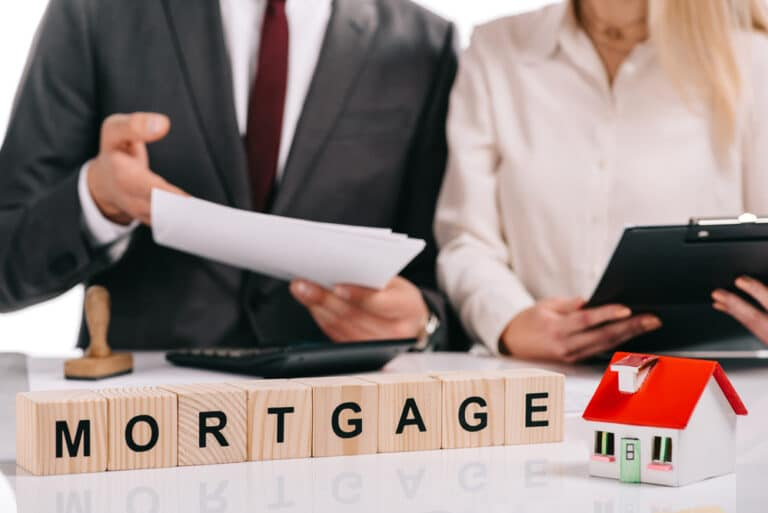 Wood blocks spelling MORTGAGE, tiny house model, man showing woman papers, woman holding clipboard