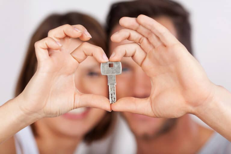 Close-up of young couple holding house key and forming heart with their hands