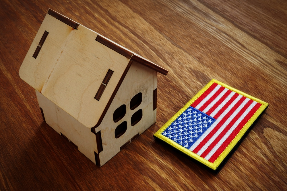 Wood model of house beside American flag patch