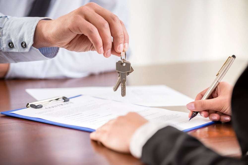 Close-up of signing papers and handing over home keys
